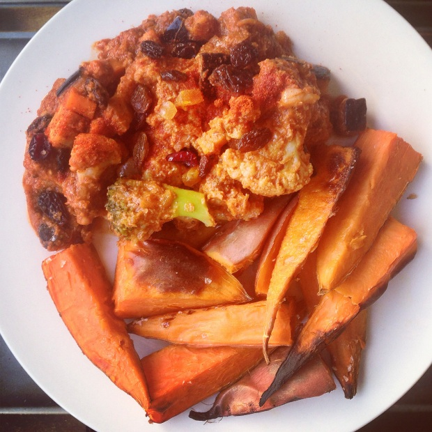 A vegetarian curry, jewelled with sultanas and served with potato wedges