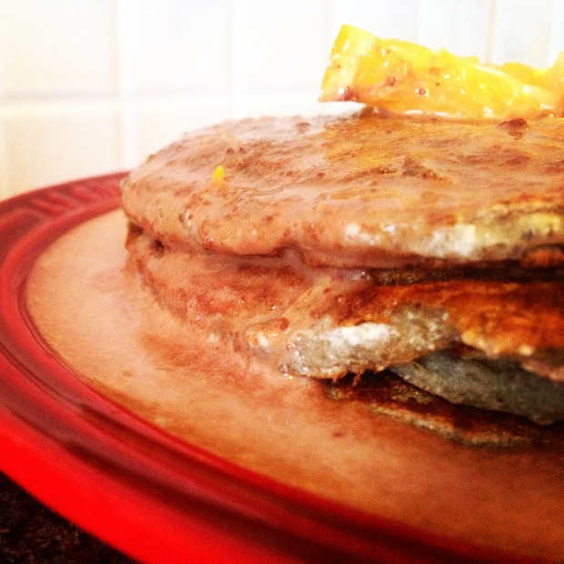 Side view of a stack of vegan paleo pancakes covered in a cacao & orange sauce, topped with a slice of orange.