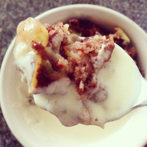A close up of a spoon with paleo crumble and custard