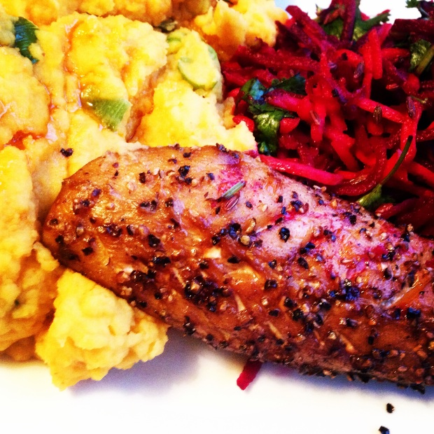 A close up of a plate of paleo spiced sweet mash, peppered mackerel and a beet, carrot and ginger salad